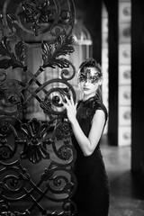 Mysterious woman in venetian carnival mask near wrought iron gate. Noir style