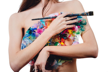 Nude attractive young female artist is holding a color palette and brush, looking at camera. studio white background.