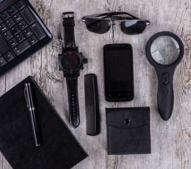 black men's items on a wooden table, a watch, a notebook, glasses, fountain pen and cell phone, businessman