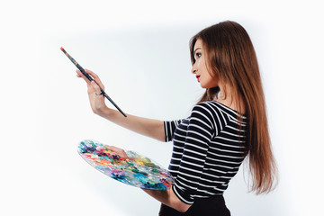 Cute beautiful girl artist holding a palette and  brush in the process draws inspiration. White background, isolated.