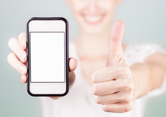 Happy woman with thumbs up, and holding blank smartphone.