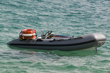 Modern inflatable boat with engine in the sea near shore