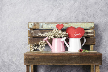 Love concept of red heart and gypsophila in watering can on wood old chair