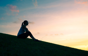 Thoughtful young woman watching the sunset. Peaceful moment's  and thinking concept.