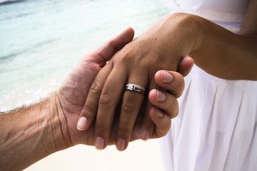 Man holding woman's hand with wedding ring