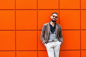 Young confident hipster man with beard in glasses posing on the orange background. Outdoor. Cute man wearing a vest, black shirt and light trousers. Man keeps hands in pockets and looking forward