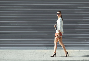 Well dressed female fashion model walking down the street.