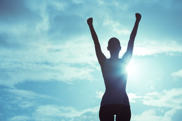 Female winning concept. Strong and confident woman raising her hands up in the air.  Wall mural