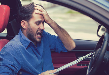 Stressed desperate man driver with papers sitting inside car