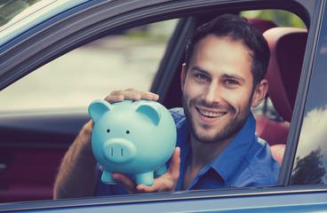 Happy man sitting inside his new car holding piggy bank
