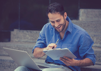 Busy man working on laptop outside corporate office
