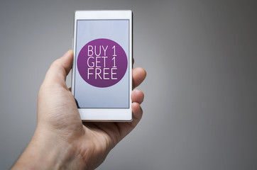 Buy one get one free icon on smart phone in hand gray background