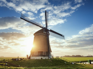 Windmill and silhouette of a man at sunrise in Netherlands. Beautiful old dutch windmill against colorful sky with clouds. Spring landscape in the morning in Holland. Rural scene. Travel background