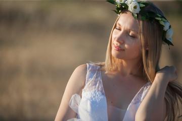 Portrait of beautiful romantic bride walking on summer sunset meadow