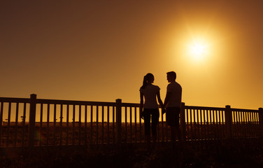 Loving couple standing in open field holding hands.