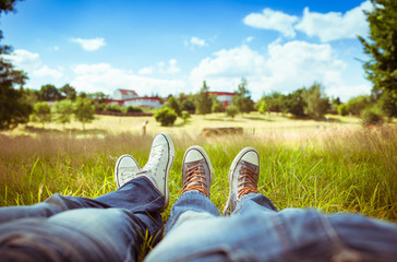 Love and relationships. Couples feet relaxing in a park on a sunny summer day.