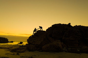Two people climbing up the cliff teamwork help to succsess