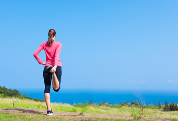 Female runner doing front thigh leg stretch.