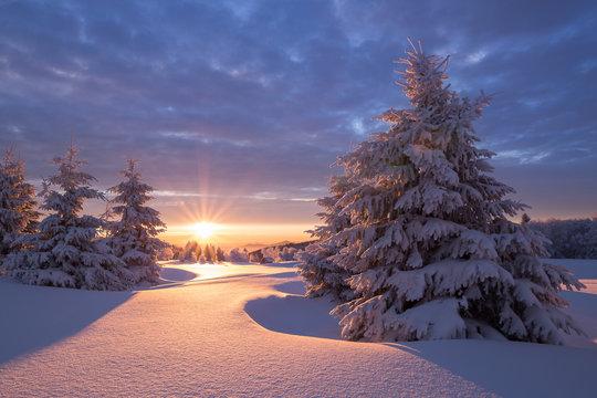 Wunderschöner Sonnenaufgang an einem kalten Wintertag im Erzgebirge mit einer kleinen Holzhütte im Hintergrund