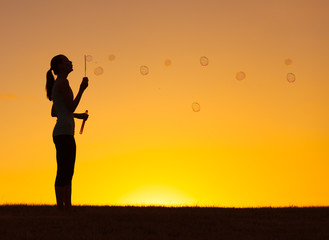 Silhouette of girl blowing bubbles/