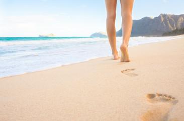 Closeup of woman's feet walking on a beach in Hawaii.