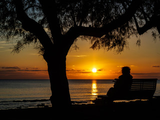 Silhouette of a person sitting on the bench by the sea, enjoying the sunset in Novigrad, Croatia