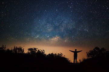 milky way galaxy and silhouette of a standing happy man on Doi L