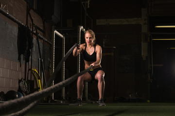 Athletic woman working out with a rope at gym.