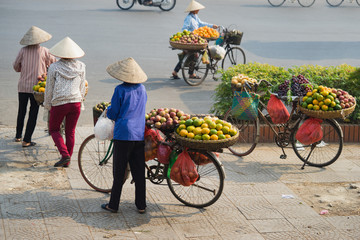 Vietnamese vendors with tropical fruit loaded basket on bike