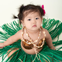 Cute Asian Chinese baby girl dressed in Hawaiian outfit.