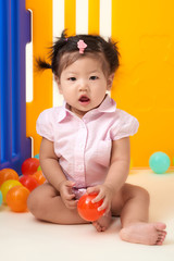Asian Chinese baby girl playing with colorful balls fenced.