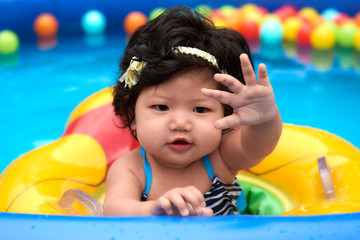 Asian baby girl in swimsuit and float swimming in pool with balls