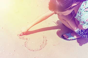 Beautiful young woman sitting on the beach and making heart shap