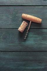 Photo of wine corkscrew and cork on dark background