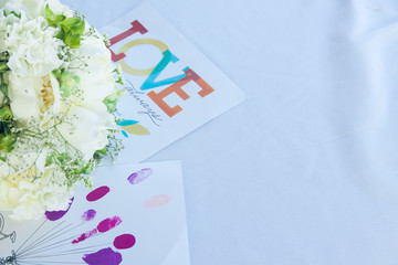 Cards and wedding bouquet on the white table