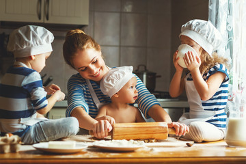 happy family in kitchen. mother and children preparing dough, ba