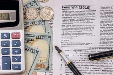 tax form w4  with pen and us dollar, calculator and pen.