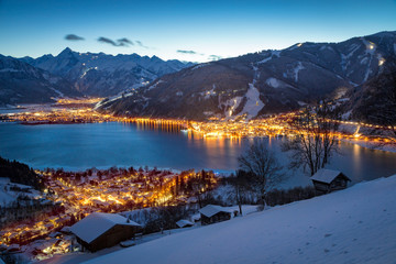 View over Zell am See mountain village at night in winter, Salzb