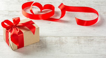 Box with a present to the Valentine's Day  and red tape on a white wooden table. Copy space