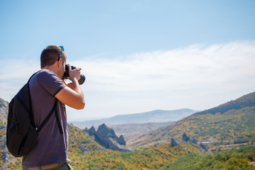 Man photographing mountain in summer