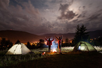 Night camping. Couple stands holding hands lifting up from enjoying the beautiful views of night cloudy sky and a glowing town between the mountains