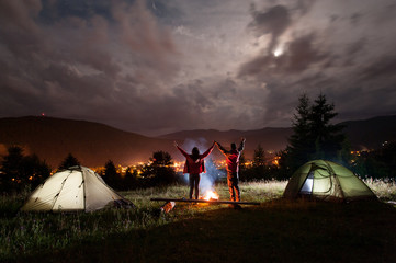 Night camping. Romantic couple standing and holding hands lifting up from enjoying the beautiful views of evening cloudy sky and a glowing town between the mountains
