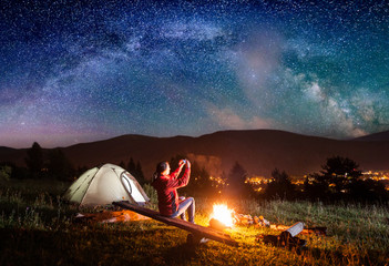 Hiker woman sitting on boards by a campfire near tent and makes the photo incredible view of night sky with stars and Milky way on the phone