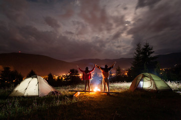 Night camping. Pair tourists stands and holding hands lifting up from enjoying the beautiful views of evening cloudy sky and a glowing town between the mountains