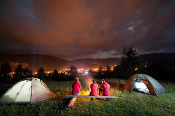 Young people sitting on a bench made of logs and watching fire together beside camp and tents in dark on the background mountains and luminous town. Rear view