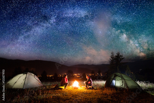 Romantic couple sitting at a c&fire near tents in the night under incredibly beautiful starry sky & Romantic couple sitting at a campfire near tents in the night ...