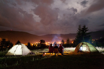 Three tourists sitting on boards around the campfire near tents at night in the background of cloudy sky, mountains and luminous town