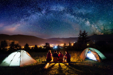 Photo sur Plexiglas Camping Friends hikers sitting on a bench made of logs and watching fire together beside camp and tents in the night. On the background beautiful starry sky, mountains and luminous town. Rear view