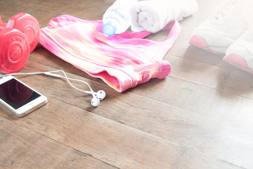 Set of workout equipment and accessories for woman on wood floor