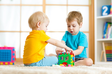 Kids toddler preschooler boys playing logical toy learning shapes and colors at home or nursery